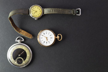 Set of watches on black background with a classic gold pocket watch a black and silver pocket watch and a wristwatch with worn leather straps