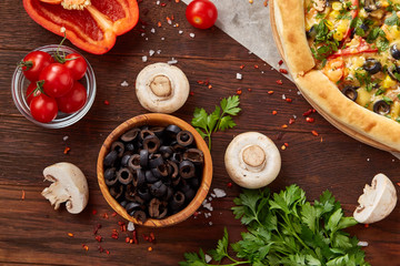 Pizza still life. Freshly baked pizza and its components arranged on wooden background.
