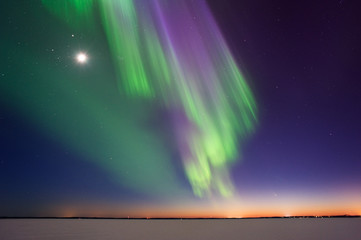 Northern Lights and Moon above frozen lake after sunset in eastern Finland