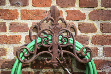 Garden hose hangs on an old ornate hook