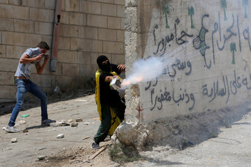 Palestinian protester releases fireworks towards Israeli troops during clashes near Hebron in the occupied West Bank
