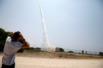 An Israeli man looks on as an Iron Dome launcher fires an interceptor rocket in the southern Israeli city of Ashkelon