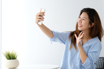 Young asian woman using smartphone to selfie her portrait at home, poeple and technology, lifestyle