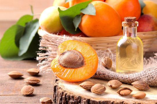 Apricot seed oil on a wooden stand next to fresh apricots on a brown wooden background