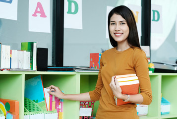Young asian woman holding books standing at library background, education concept