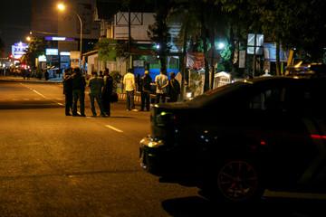 Indonesian police stand near the scene of a shooting in Sleman, Yogyakarta