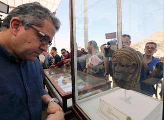 Minister of Antiquities Khaled al-Anany stands near the display case of a silver mask at a newly discovered burial site near Egypt's Saqqara necropolis,in Giza
