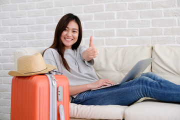 Young asian woman traveler using laptop and smiling with ok guster hand sign, blogger, travel summer holiday vacation concept