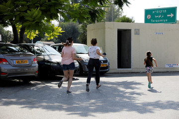 Israelis run for shelter as a siren sounds during a rocket attack near Yad Mordechai at the Israeli side of the Israel Gaza border