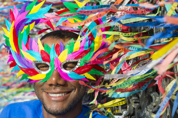 Carnival scene features smiling Brazilian man in colorful mask with wish ribbons.