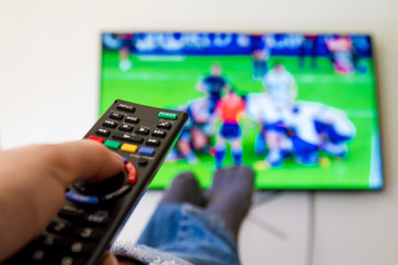 Close-up macro of man's hand with TV remote control watching a rugby match