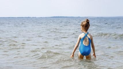a girl in a blue swimsuit walks along the seashore