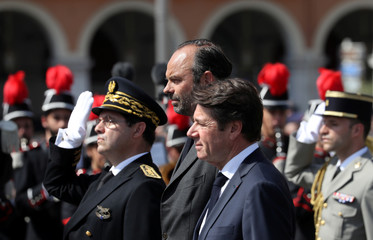 French Prime Minister Edouard Philippe stands with Mayor of Nice Christian Estrosi as he reviews an honour guard of troops, in Nice