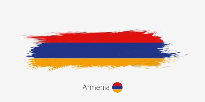 Flag of Armenia, grunge abstract brush stroke on gray background.