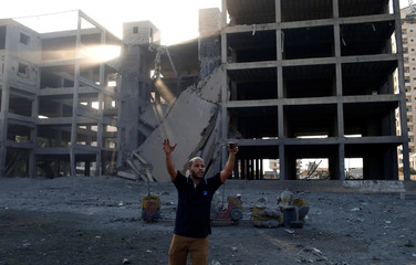 Palestinian man reacts following an Israeli air strike on a building in Gaza City