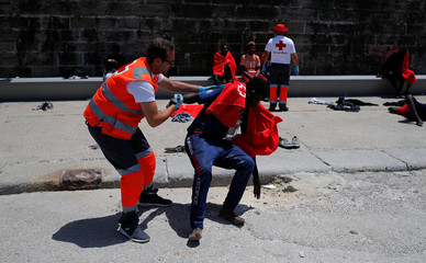 A migrant is helped by a member of Spanish Red Cross after arriving on a rescue boat at the port of Tarifa