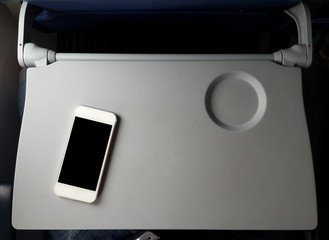 Poster Avion à Moteur Airplane tray table on seat back with smartphone