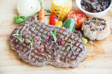 Spicy beef steak on wooden platter