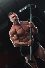 Mature bodybuilder with strong relief body posing in gym