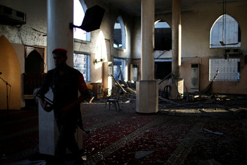 Palestinian security man inspects a mosque damaged in nearby Israeli air strikes in Gaza City