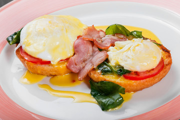 English breakfast- Fried bread toast with egg, spinach, tomatoes, mozzarella cheese and ham on plate on dark wooden background