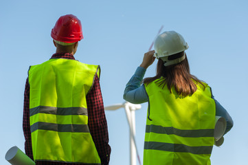 Rear-view engineers - man and woman in green vests holding helmets and looking at a windmill evaluating the work of their project