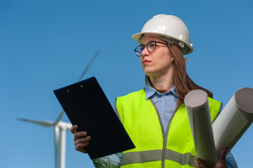 Portrait of a successful young female engineer in a safety helmet with a work plan and projects on a background of windmills and blue sky.