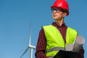 Portrait of a successful young male engineer in a safety helmet with a work plan and projects on a background of windmills and blue sky.