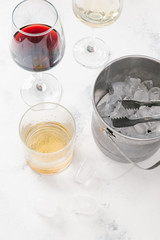 Glasses with red and white wine, glass of whisky and pot with ice cubes on white concrete background