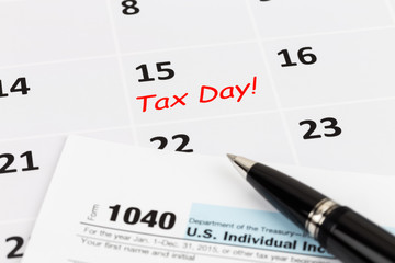 Tax day on calendar with pen, and tax form