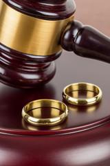 Wooden judge gavel and golden rings divorce concept