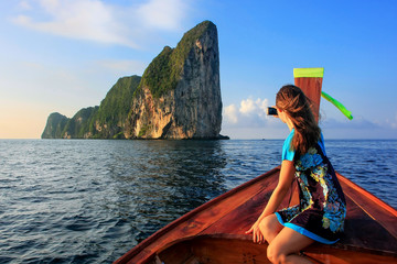 Young woman sitting in the front of a longtail boat going to Phi Phi Leh Island, Krabi Province, Thailand