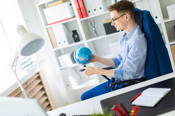 A young man sits in the office at a computer desk and holds a globe in his hands.