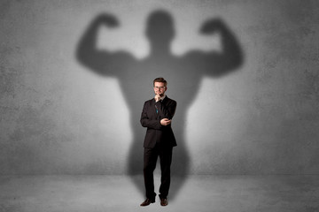 Fototapeta Lovely serious businessman standing with a muscular powerful shadow behind his back