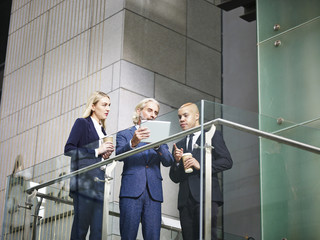 multinational and multiethnic corporate executives discussing business using digital tablet