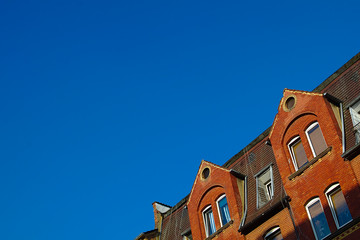Gable of a red house in front of a clear blue sky in the summer