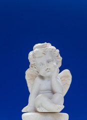 Figurine Of Baby Angel On Blue Background