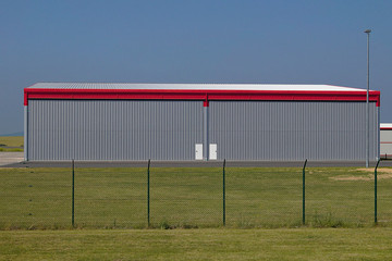 Big hangar with red lines, green grass in ghe front and blue sky