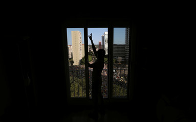 A woman closes a window during a protest against the imprisonment of the Catalan separatist leaders, in Barcelona