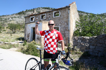 Man poses in front of Luka Modric's birth house in Modrici village