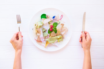 Top view female hands holding knife and fork over the plate with unreal salad from recycle waste, synthetic ingredients. Concept of artificial, food. GMO, E numbers . Chemicals in the food industry.