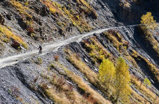 Cyclist man riding mountain bike  on a mountain road