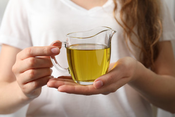 Young woman holding jug of fresh olive oil, closeup