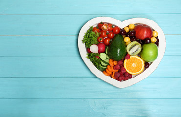 Heart shaped plate with fresh fruits and vegetables on wooden background, top view. Cardiac diet