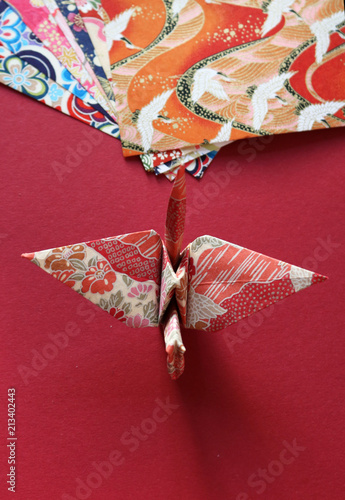 Top View Of A Colorful Japanese Origami Paper Crane On A Bright Red Simple Patterned Origami Paper