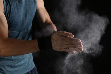 Young man applying chalk powder on hands against dark background