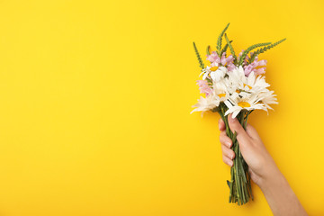 Woman with wild flowers on color background, top view