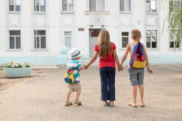 Children go back to school. Start of new school year after summer vacation. Boy and girl with school bags are playing in park near the school building. Education for kindergarten and preschool kids.