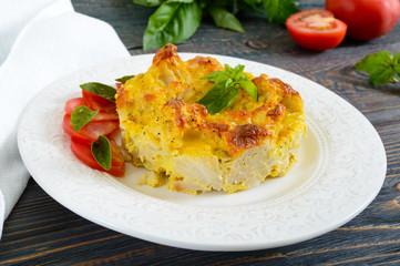 Tasty useful casserole from cauliflower on a plate on a dark wooden background. Vegetarian menu. Proper nutrition.