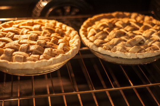 Two homemade apple pies baking in an oven on the top rack.  Horizontal image.